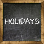 Holidays handwritten on blackboard — Stock Photo