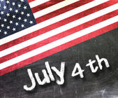 July 4 th handwritten with white chalk on a blackboard — Stock Photo