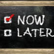 Now or later written with white chalk — Stock Photo