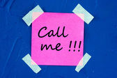 Call me, written on pink sticky paper sticked on blue wall — Stock Photo