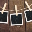 Photo paper attach to rope with clothes pins on wooden background — Stock Photo