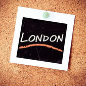 Instant photo pined on cork with London — Stock Photo