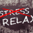 Crossing out stress and writing relax on a blackboard. — Stock Photo