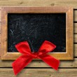 Wooden frame with a red bow — Stock Photo #34221065
