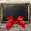 Wooden frame with a red bow — Stock Photo #34221175