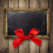 Wooden frame with a red bow — Stock Photo #34221215