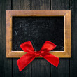 Wooden frame with a red bow — Stock Photo #34221281