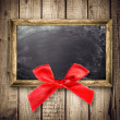 Wooden frame with a red bow — Stock Photo #34221863