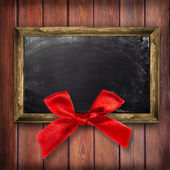 Wooden frame with a red bow — 图库照片