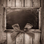 Wooden frame with a red bow — Stock Photo