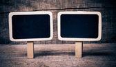 Small wooden framed blackboard on wooden background — Stock Photo
