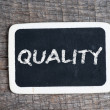 Quality handwritten with white chalk on a blackboard — Stock Photo #37626655