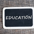 Education handwritten with white chalk on a blackboard — Stock Photo
