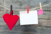 Blank instant paper shit and heart hanging on the clothesline — Stock Photo