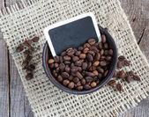 Chicchi di caffè in una ciotola di legno sul panno su fondo in legno — Foto Stock