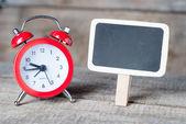 Alarm clock next to small blackboard — Stock Photo