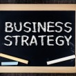 Business strategy handwritten with white chalk on a blackboard — Stock Photo