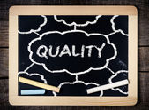 Quality handwritten with white chalk on a blackboard — Stock Photo