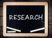 Research handwritten with white chalk on blackboard — Stock Photo