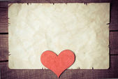Wooden heart on old paper — Stockfoto