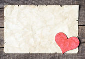 Wooden heart on old paper — Stock Photo