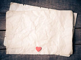 Wooden heart on old paper — Стоковое фото