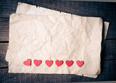 Wooden hearts on old paper — Stock Photo