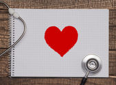 Wood texture background with stethoscope and heart symbol — Stock Photo