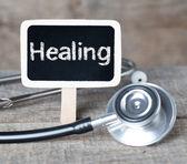 Healing word on blackboard on wooden background — 图库照片