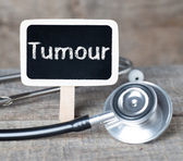 Tumour word on blackboard on wooden background — Stock Photo