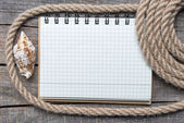 Ship rope, sea shells, notebook and old wood background — Stock Photo