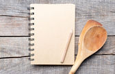 Old recipe notebook, spoons on wood background — Stock Photo