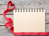 Blank notebook paper with heart ribbon — Stock Photo