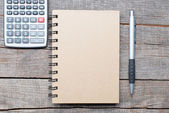 Calculator, pen and notebook on wooden table — Stock Photo