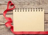 Blank notebook paper with heart ribbon on wooden table — ストック写真