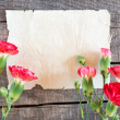 Sheet of notebook and red and white carnations flowers — Stock Photo #42391997