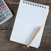 Office table with pen, calculator and empty paper — Stock Photo