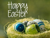 Easter eggs in wisker basket in nature with text Happy Easter — Stock Photo