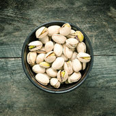 Pistachios in wooden bowl — Stock Photo