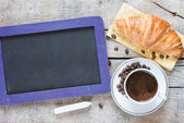 Blackboard with croissant and coffee — Stock Photo