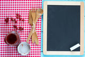 Blackboard on wooden surface — Stock Photo