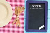 Blackboard with menu sign on wooden surface — Stock Photo