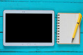 Tablet with blank screen and notepad — Stock Photo