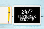 Tablet PC with words 24-7 customer services — Stock Photo
