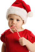 Close up of little girl licking a candy cane — Stock Photo
