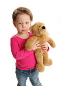 Child holding a teddy bear with mad expression — Stock Photo