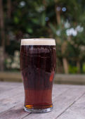 Pint of bitter on pub garden table — Stock Photo