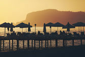 Silhouette of chairs and umbrellas on deck. Summer resort — Stock Photo