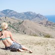 Stock Photo: Girl sitting and looking at the sea, the mountains