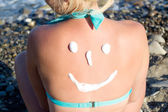 Sun protection cream on her back — Stock Photo